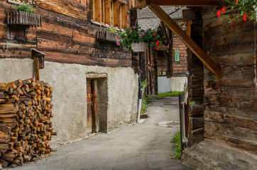 Wooden houses and sheds in rural village in Swiss alps in Valais valley on a summer day. Peaceful and traditional Swiss town