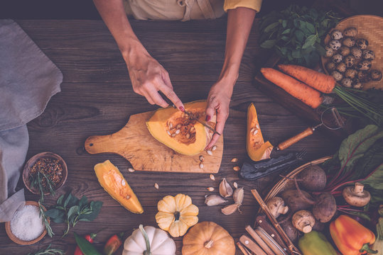Woman hands cutting vegetables on rustic wooden background. Vegetables cooking ingredients, top view, copy space, flat lay.