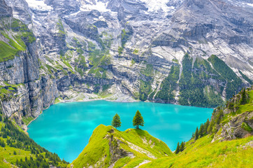 Beautiful top view of Oeschinensee, Oeschinen Lake by Kandersteg, Switzerland. Turquoise lake with steep mountains and rocks in background. Swiss Alps. Switzerland summer. Tourist destinations