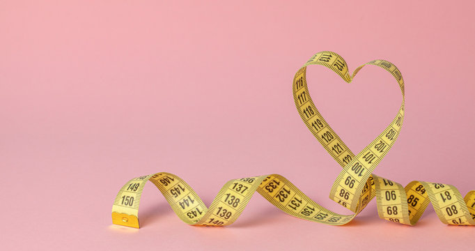 Yellow measuring tape in the shape of a heart on a pink background. The concept of weight loss for the normal functioning of the heart and body. Copy space for text.