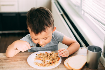 The child eats pilaf with carrots in the kitchen during the day