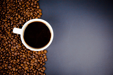 cup of coffee with beans on black background