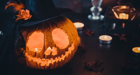 Close up carved pumpkin in witch hat, burning candles and silhouettes of bats, castle, ghosts on black stone background. Head jack lantern with scary evil faces. Spooky holiday concept. Wide banner.