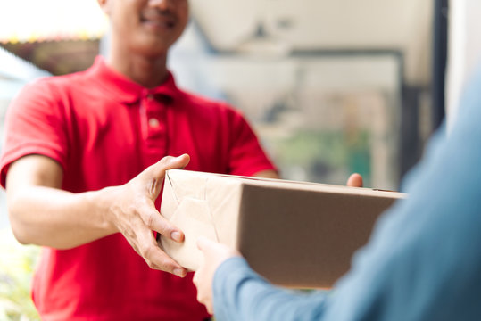 Postman delivering package of goods to home with smile and happy face. Young Asian cute girl receiving boxes from postman at the door. Selective focus on the hands. Home delivery concept.