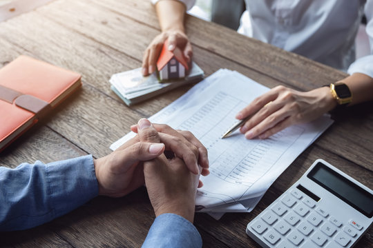 Loan agreement, real estate agent or bank officer describes the loan interest to the customer, along with loan documents with a home-style pen and a replica money on a wooden table.