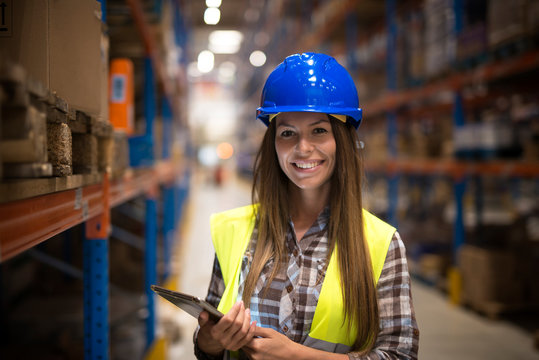 Portrait of smiling woman in protective uniform with hardhat holding tablet in warehouse center.
