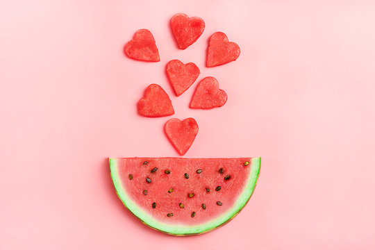Red watermelon pattern. Creative layout made in shape of heart of fresh watermelon on pastel pink background. Summer, food concept. Flat lay, top view, copy space Minimal style