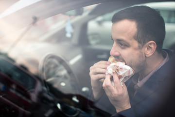 Handsome young man eating a hurried lunch in his car (color toned image; shallow DOF)
