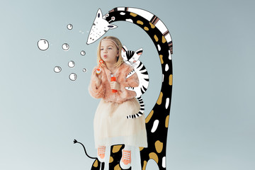 adorable kid in faux fur coat and skirt sitting on fairy giraffe and blowing soap bubbles isolated on grey
