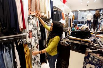 An Iraqi woman looks at a dress at a shop ahead of the Eid al-Adha festival in Baghdad