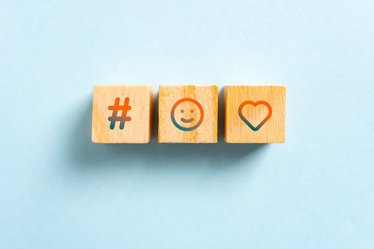 Social media icons. Hashtag, happy smiling face and heart icons on wood blocks toys and blue background. Rating and viral concept.