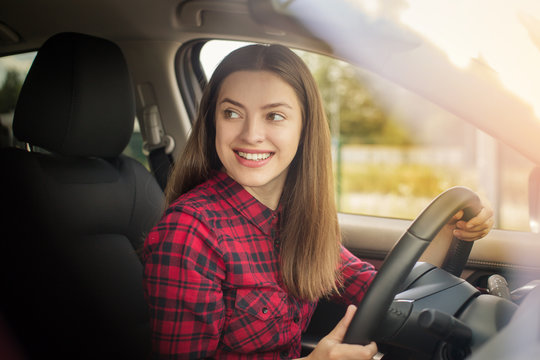 Attractive young woman in casual wear smiling while driving a car