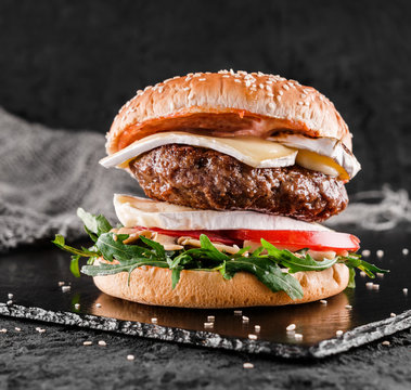 Tasty burger with cheese brie, blue cheese, mozzarella, tomatoes and arugula on slate black background, close up