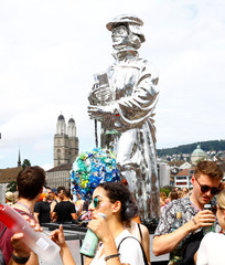 A statue of Swiss reformer Ulrich Zwingli is carried on a float as the Grossmuenster church is seen in the background during the Street Parade dance music event in Zurich