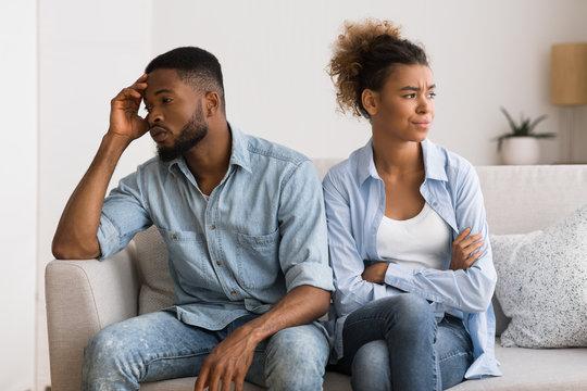 Upset Black Couple Avoiding Eye Contact Sitting On Couch