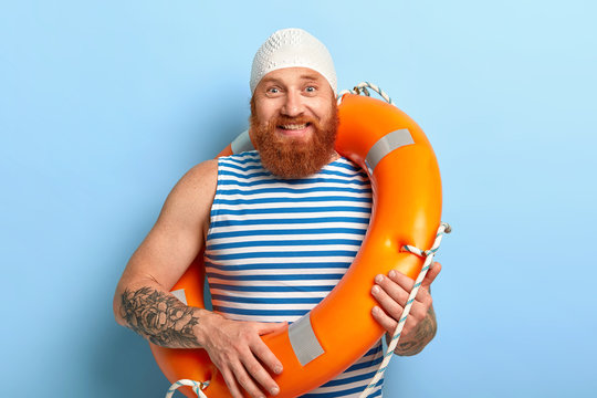 Summer vacation concept. Cheerful man with ginger beard, wears swimcap and sailor t shirt, poses with lifering, works as lifeguard at beach, has fun. Accident prevention and swimming equipment