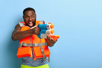 Waterfight battle. Emotional black man screams I will shoot you, holds toy water gun, has fun during summer vacation with friends, plays game at beach, dressed in lifevest, stands against blue wall