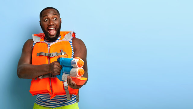 Indoor shot of emotional dark skinned man has fight with someone, plays with water gun, stares into distance with widely opened mouth, enjoys real battle, wears protective lifevest. Summer activity