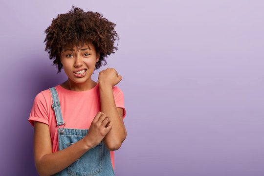 Skin problem concept. Displeased Afro female scratches itchy arm, has allergy, smirks face and looks with dissatisfaction, wears casual pink t shirt and jean overalls, stands against purple wall