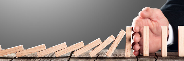 Hand of businessman Blocking Domino Effect On Wooden Table - Investment Protection And Security...