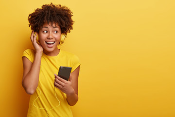 Photo of female meloman listens favourite playlist in headphones, enjoys good sound, holds cellular with multimedia application, wears bright casual clothing, isolated on yellow background. Monochrome