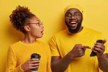 Excited surprised woman listens with great interest male model who tells about great opportunities and functions of new smartphone, points in display, wear yellow outfit in one tone with background