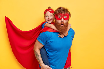 Superheroes team ready to save our world. Little kid girl rides back of her father superhero, pretend flying, wears red cape, special mask, isolated on yellow background. Success, motivation, win