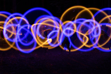 Asbstract colorful neon shapes made with LED poi. Long exposure light painting.