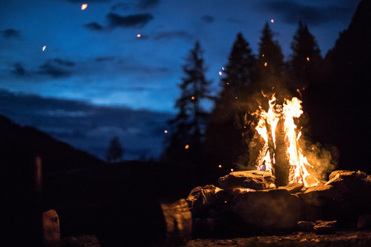 Camping bonfire with yellow and red flames in summer, forest. Copy space.