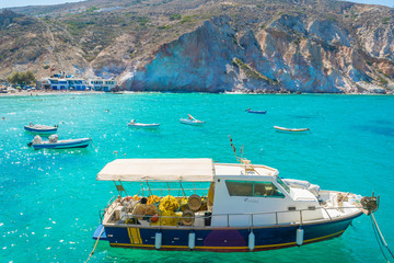Crystal clear turquoise waters of the bay of Firopotamos village with traditional fishing boats in Milos, Cyclades, Greece