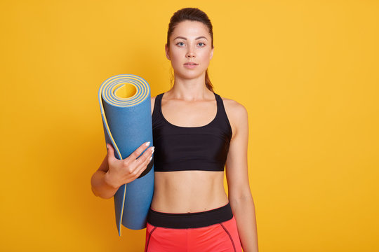 Sporty girl holding yoga mat in hands, wearing pants and black bra, looking directly at camera, looks serious, posing over yellow studio background. Fashion, sport and healthy lifestyle concept