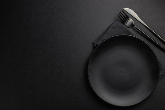 Elegant black table setting: plates, napkin and silverware over black background. Flat lay. copy space