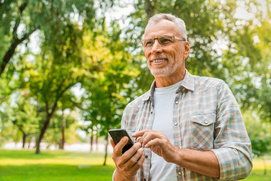 Low angle view of mature man standing outdoors using mobile phone