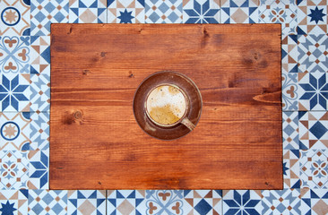 Cup of cappuccino on wooden table. Still life detail in home interior. Wooden table with cup of coffee on it and colorful tiles top view