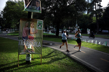 Women run in front of a campaign sign for the National Unity of Hope (UNE), ahead of the second round run-off vote, in Guatemala City
