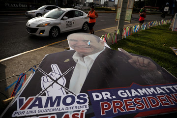 "A woman runs in front of a campaign signs for Alejandro Giammattei, presidential candidate of ""Vamos"" political party, ahead of the second round run-off vote, in Guatemala City"