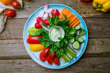 slicing fresh vegetables on a plate on wooden table