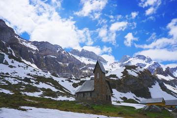 Alte Steinkirche in den Bergen vor blauem Himmel mit weißen Wolken