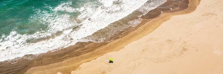 Aerial view of a sandy beach with a yellow umbrella in Huarmey, Ancach region, Peru.