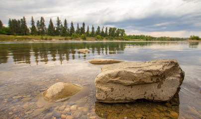 Few single, large rocks peaking out of the calm waters on the river, rain and forest in the background