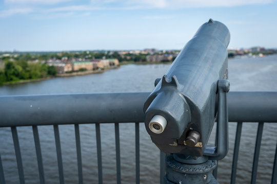 A telescope is mounted on a scenic vista along the Woodrow Wilson Bridge, overlooking the cities of Alexandria, Virginia and Washington, DC
