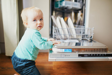 Little child helping to unload dishwasher