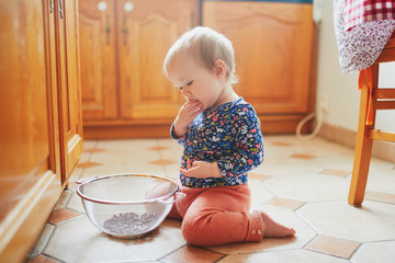 Baby girl sitting on the floor in the kitchen and playing with kitchenware