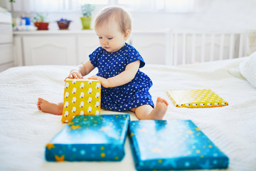 girl in blue dress celebrating her first birthday and unpacking her presents