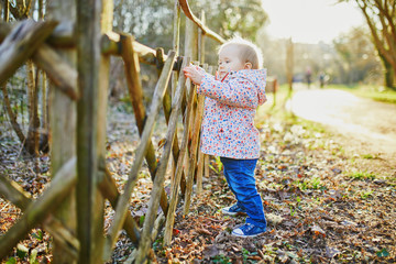 One year old girl standing next to wooden fence in park