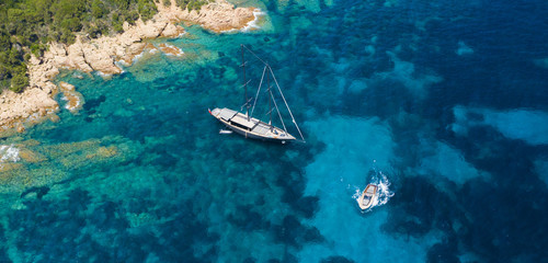 Fototapete - View from above, stunning aerial view of a luxury sailboat floating on a beautiful turquoise clear sea that bathes the green and rocky coasts of Sardinia. Emerald Coast (Costa Smeralda) Italy.