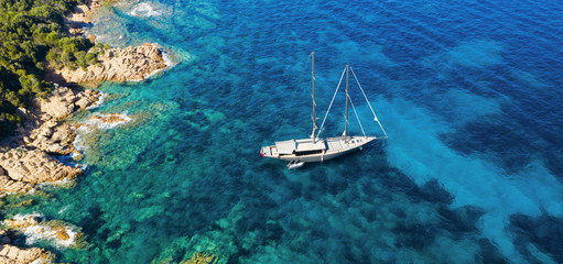 Wall Mural - View from above, stunning aerial view of a luxury sailboat floating on a beautiful turquoise clear sea that bathes the green and rocky coasts of Sardinia. Emerald Coast (Costa Smeralda) Italy.