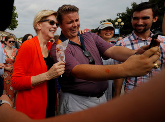 Democratic 2020 U.S. presidential candidate Warren poses for a photograph holding a corn dog at the Iowa State Fair in Des Moines