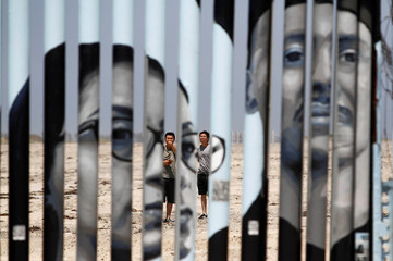 Tourists are seen behind a section of the wall separating Mexico and the United States, in this picture taken from the Mexican side of the border in Tijuana