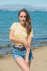 Brunette in yellow and blue by the bay
